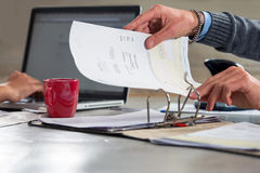 Filing invoices and documents in a ring binder. People, fining documents and doing their administration, working on a laptop and filing invoices and bills in a Stock Photos
