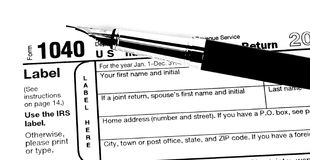 Filing out a tax form. A fountain pen ready to fill out a 1040 tax form Stock Photo