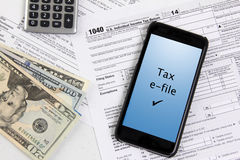 Filing taxes using a mobile phone. E-file taxes with mobile phone Royalty Free Stock Photo