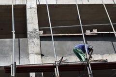 Filipijnse bouwmetselaar het pleisteren pleister aan boord van steigerpijpen op high-rise die alleen bouwen royalty-vrije stock foto