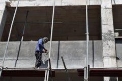 Filipijnse bouwvakker die de steigers van de metaalpijp installeren bij high-rise de bouw alleen zonder beschermend kostuum royalty-vrije stock fotografie