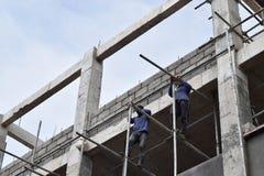 Filipijnse bouwvakkers die de steigers van de metaalpijp installeren bij high-rise de bouw zonder beschermend kostuum royalty-vrije stock fotografie