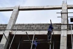 Filipijnse bouwvakkers die de steigers van de metaalpijp installeren bij high-rise de bouw zonder beschermend kostuum stock afbeeldingen