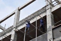 Filipijnse bouwvakkers die de steigers van de metaalpijp installeren bij high-rise de bouw zonder beschermend kostuum royalty-vrije stock foto