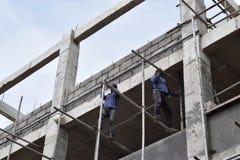 Filipijnse bouwvakkers die de steigers van de metaalpijp installeren bij high-rise de bouw zonder beschermend kostuum stock foto