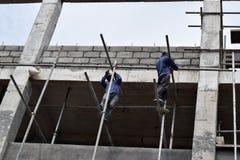 Filipijnse bouwvakkers die de steigers van de metaalpijp installeren bij high-rise de bouw zonder beschermend kostuum stock afbeelding