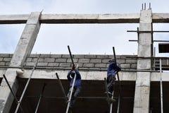 Filipijnse bouwvakkers die de steigers van de metaalpijp installeren bij high-rise de bouw zonder beschermend kostuum royalty-vrije stock foto's
