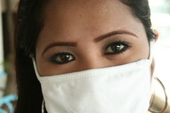 Filipina and bird flu. A filipina wearing a surgical mask to prevent the bird flu Royalty Free Stock Photo