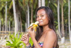 Filipina girl eating banana Stock Photo