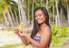 Filipina girl eating banana Stock Images