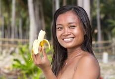 Filipina girl eating banana Stock Image