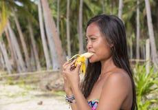 Filipina girl eating banana Royalty Free Stock Images