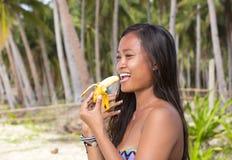 Filipina girl eating banana Royalty Free Stock Image
