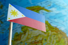 Filipinas señalan por medio de una bandera con un mapa del globo como fondo Fotos de archivo libres de regalías