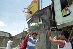 Filipino boys play basketball in slum, Manila royalty free stock image
