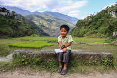 Filipino child in banaue. Filipino child back from school in the rice field background Royalty Free Stock Photo