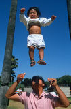 Filipino father tossing baby in the air Royalty Free Stock Image