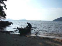 Filipino fisherman near his wooden boat. stock video