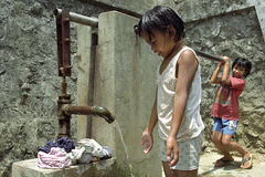 Filipino girls wash clothes at water pump Royalty Free Stock Photography