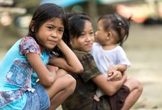 Filipino kids. Kids of a poor filipino family are sitting outdoor, one is holding her  young sister, El Nido, Philippines, on january 11, 2014 Royalty Free Stock Photo