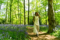 Filipino model running through a blue bell wood Royalty Free Stock Photo