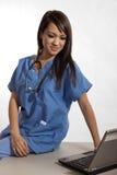 Filipino nurse doctor working on laptop Stock Photos