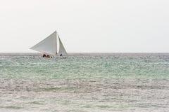 Filipino pump boat with sails. A Filipino pump boat with sails sails along the horizon of an empty calm sea Stock Photography