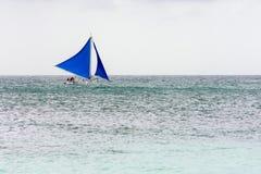 Filipino pump boat with sails. A Filipino pump boat with sails sails along the horizon of an empty calm sea Stock Images