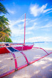 Filipino red boat on the white sand beach in Stock Photography