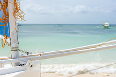 Filipino sail boat on the beach. Foreground focus of a Philippines Filipino sail boat on the beach looking out to a calm clear sea with pump boats in the back Stock Images
