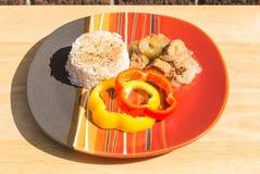 Filipino Style Pork Adobo with Jasmine Rice. Plated Filipino style Pork Adobo with jasmine rice in natural light.  Bell pepper ring garnishment Stock Photo