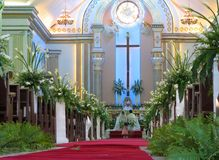 Filipino Wedding. Traditional Filipino Catholic wedding ceremony old style in a cathedral, with flowers arranged along the aisle and the couple at the altar Stock Images