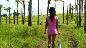Filipino woman walking along a green grass field - Philippines stock footage