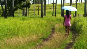 Filipino woman walking along a green grass field in the Philippines stock video