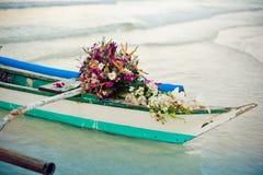 Filippijnse boot en een boeket van bloemen Huwelijk in het concept van keerkringen Royalty-vrije Stock Afbeelding