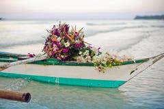 Filippijnse boot en een boeket van bloemen Huwelijk in het concept van keerkringen Royalty-vrije Stock Fotografie