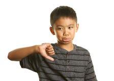 Filippinsk pojke på vit bakgrund med hans tumme ner och olyckligt uttryck Arkivfoto