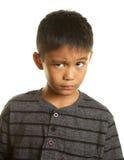 Filippinsk pojke på vit bakgrund som ser skeptisk Royaltyfri Fotografi