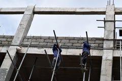 Filippinska byggnadsarbetare som installerar metall, leda i rör ställningar på höghus utan den skyddande dräkten royaltyfri bild