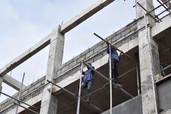 Filippinska byggnadsarbetare som installerar metall, leda i rör ställningar på höghus utan den skyddande dräkten arkivfoto