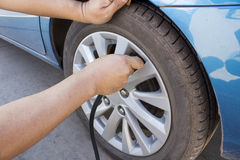 Fill air in a car's tire. In the gas station stock images