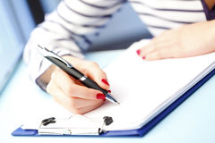 Fill the form. Close-up portrait of young businesswoman sitting at office while fill the application form on job interview royalty free stock image