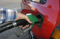 Fill her up!. Close up of the hand of a motorist, filling his car with unleaded petrol on a garage forecourt. Beyond is the empty forecourt, but reflected in the Stock Image