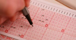 Fill out a lottery ticket hand cross out numbers. Fill out a lottery ticket hand with pen cross out numbers stock video