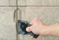 Fill the tile joints with grout. The hand of man holding a rubber float and filling joints with grout Stock Photo