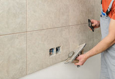Fill the tile joints with grout. Worker holding a rubber float and filling joints with grout Stock Image