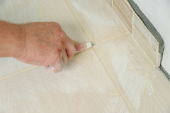 Fill the tile joints with grout Stock Photos