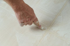 Fill the tile joints with grout. Workers hand smoothing the grout  joints between tiles using a rubber stick Royalty Free Stock Image