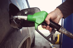 Fill up fuel at petrol station. Filling a dirty car at a gas station. Fuelling nozzle for refuelling a car in man's hand royalty free stock photo