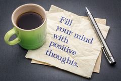 Fill your mind with positive thoughts. Inspirational handwriting on a napkin with cup of coffee against gray slate stone background Stock Photography